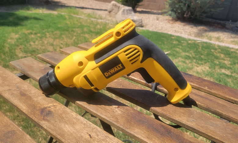 A DeWalt corded drill placed on a bench